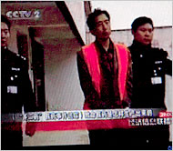 Wang Guiping, shown with police officers after his arrest