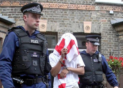 Banksy, AKA Paul Horner, seen here being taken into police custody.(AP Photo/Dennis System)